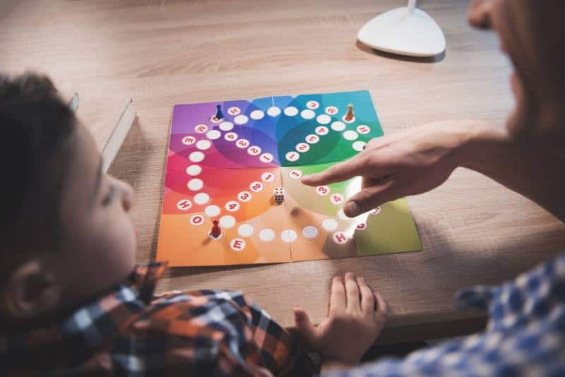 child with autism and father playing a board game