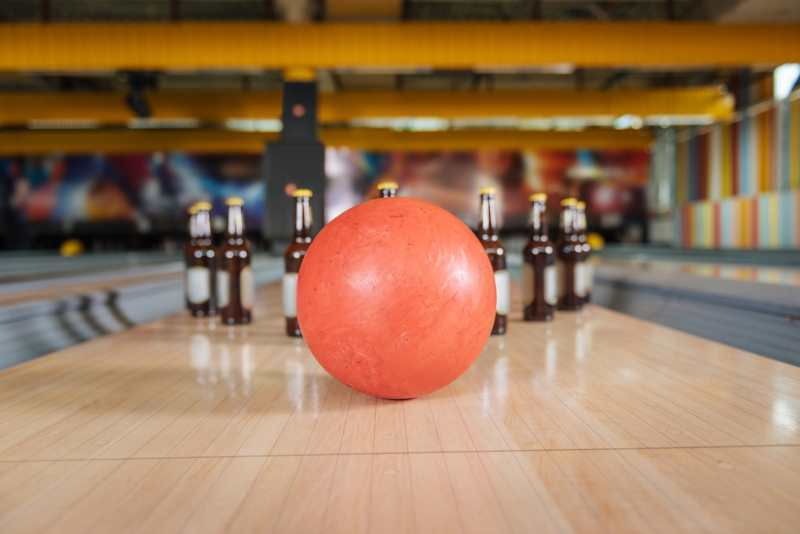 bowling ball about to hit a bunch of pins as bottles