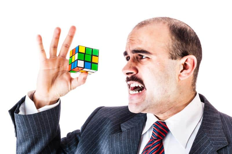 man trying to solve cube puzzle