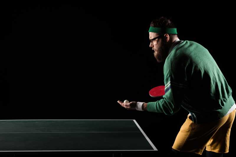 bearded man on ping pong table getting ready to serve