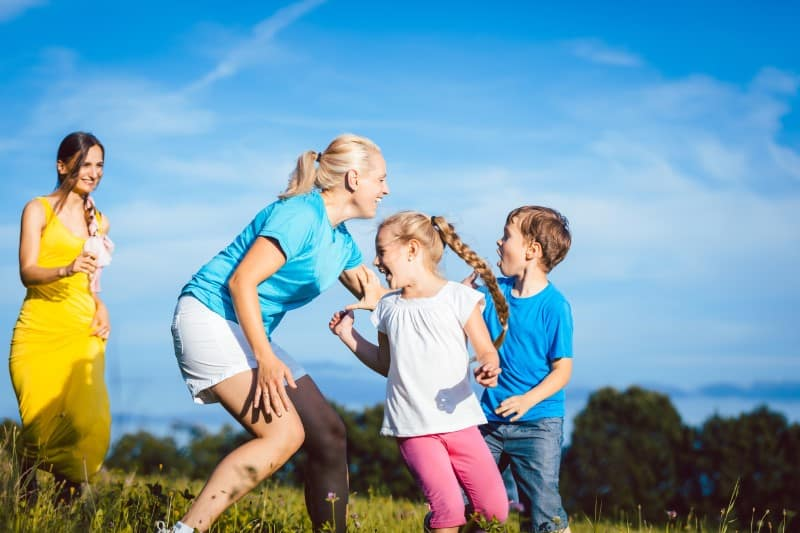 woman playing tag with children