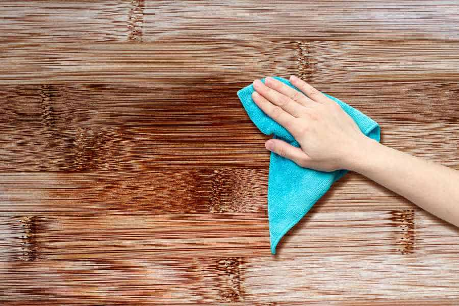 cleaning surface removing dust from shuffleboard table surface